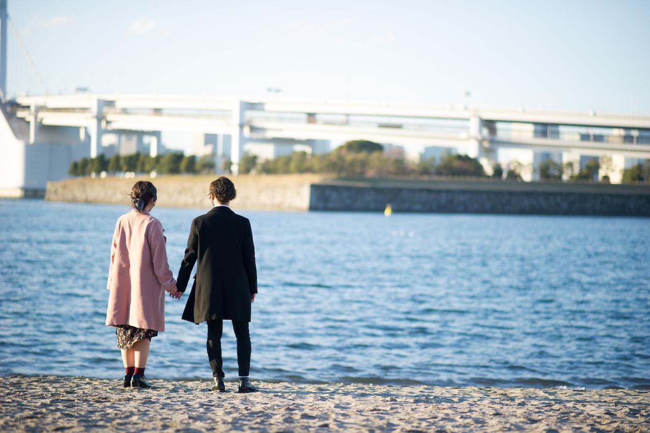 水辺で手をつなぐカップル