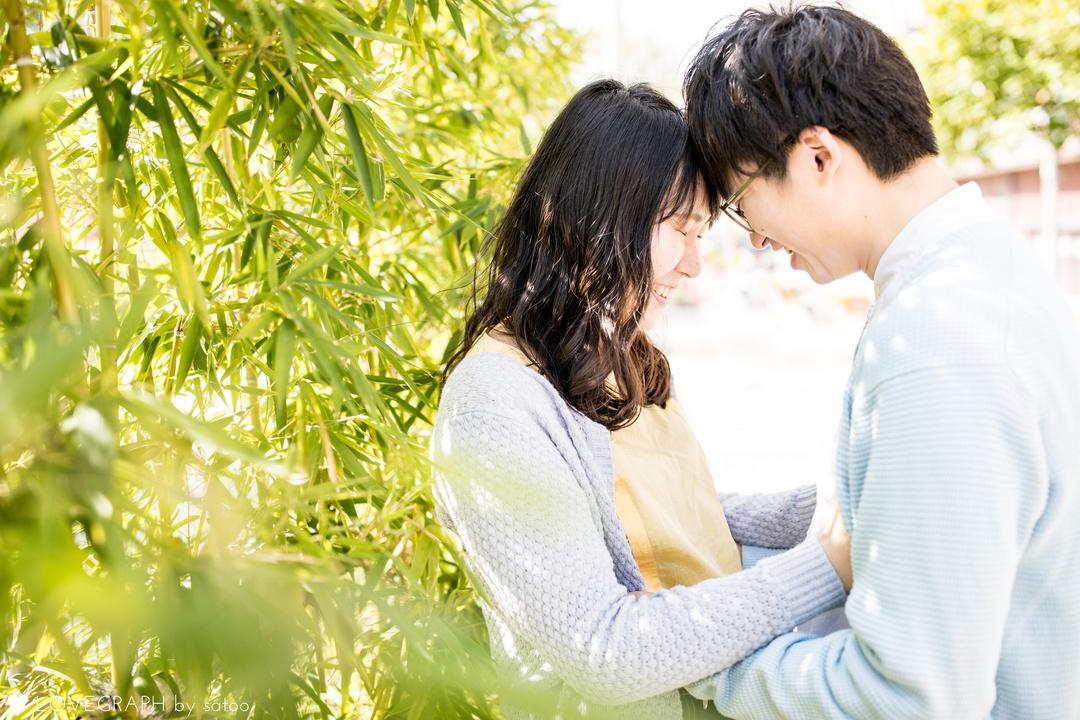 緑の葉を背に向き合うラブラブな男女