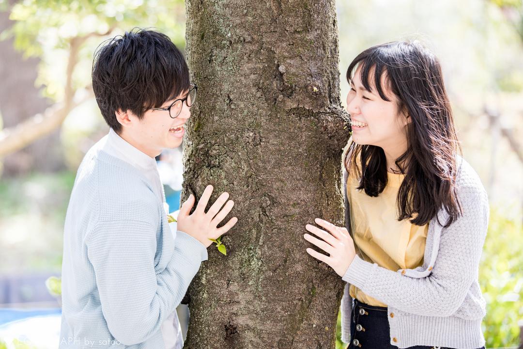 木の幹を間にはさみ、微笑み合う男女