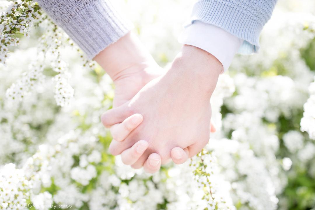 白い花を背景につなぎあう男女の手