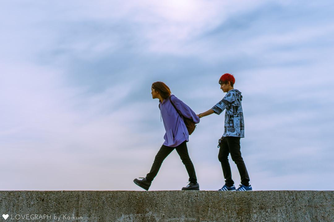 海沿いの堤防の上で、男性の手を引く女性