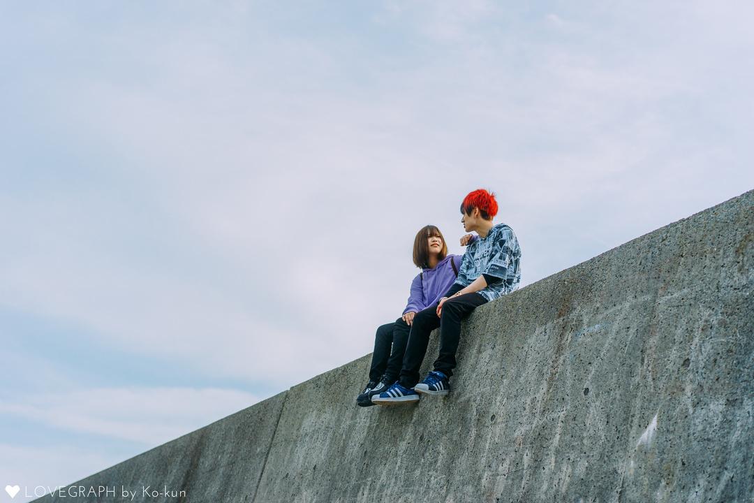 コンクリートの堤防に腰掛け、向かい合う男女