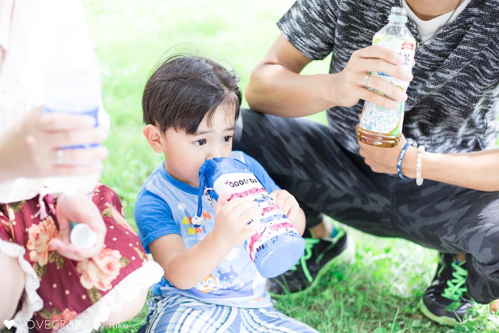 公園で飲み物を飲むカップルと子供