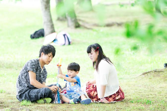 公園で子供と遊ぶカップル