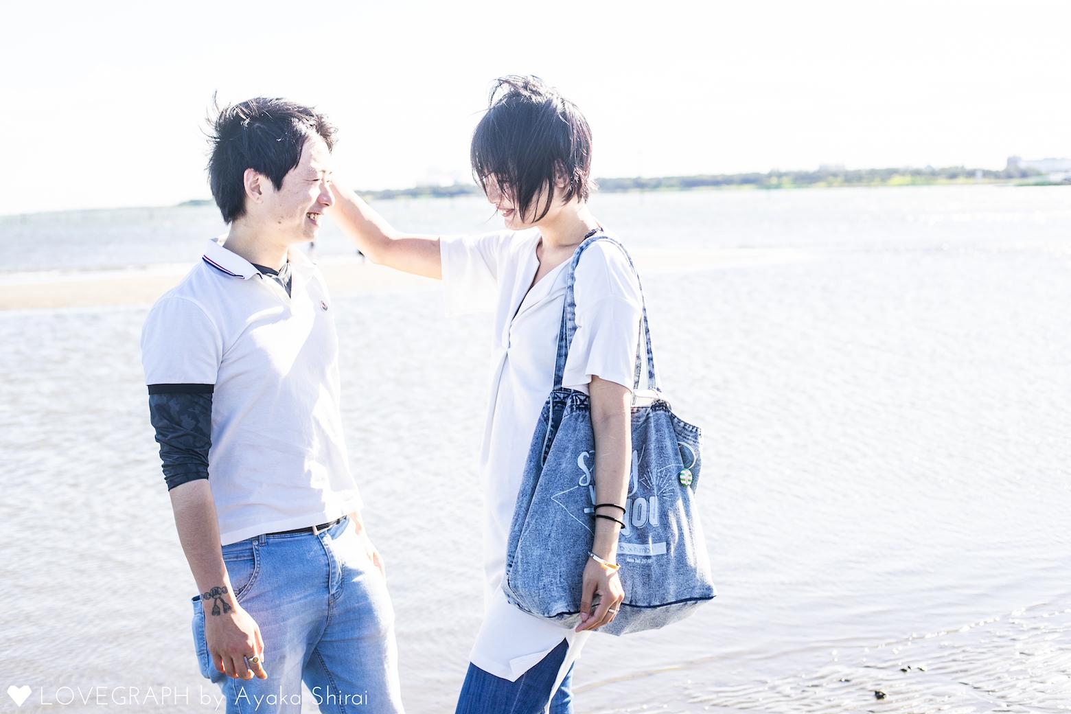 浜辺で男性の頭に手を乗せる女性