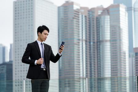 スーツを着てビルの屋上でスマホを見る男性