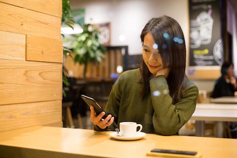 カフェでスマホを見ながら微笑む女性
