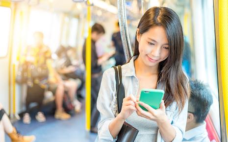 電車の中でスマホを見て微笑む女性