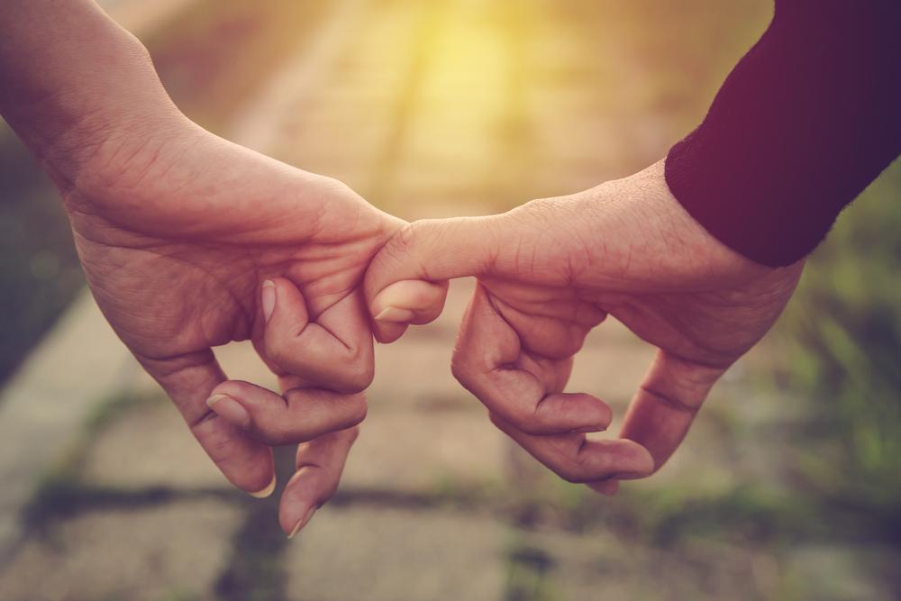 小指をつなぐ男女