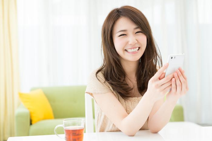 スマホを手に持って微笑む女性