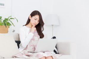 パソコンを見つめ悩む女性