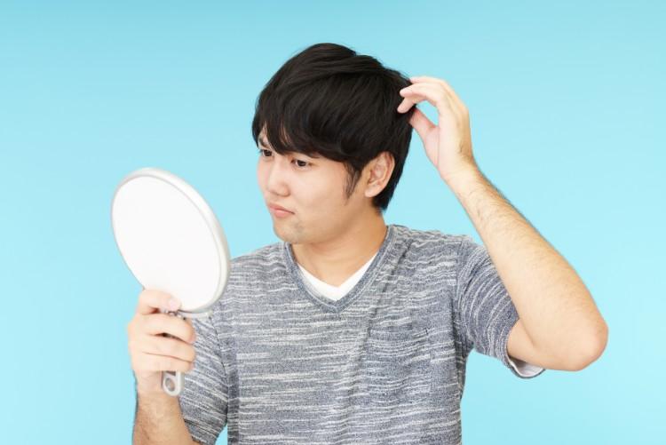 鏡を見て悩む男性