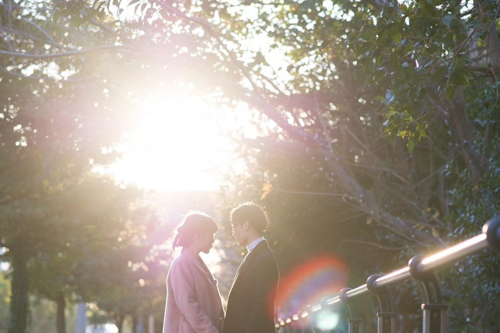 木漏れ日と向かい合うカップル