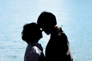 海バック_額を寄せるカップル