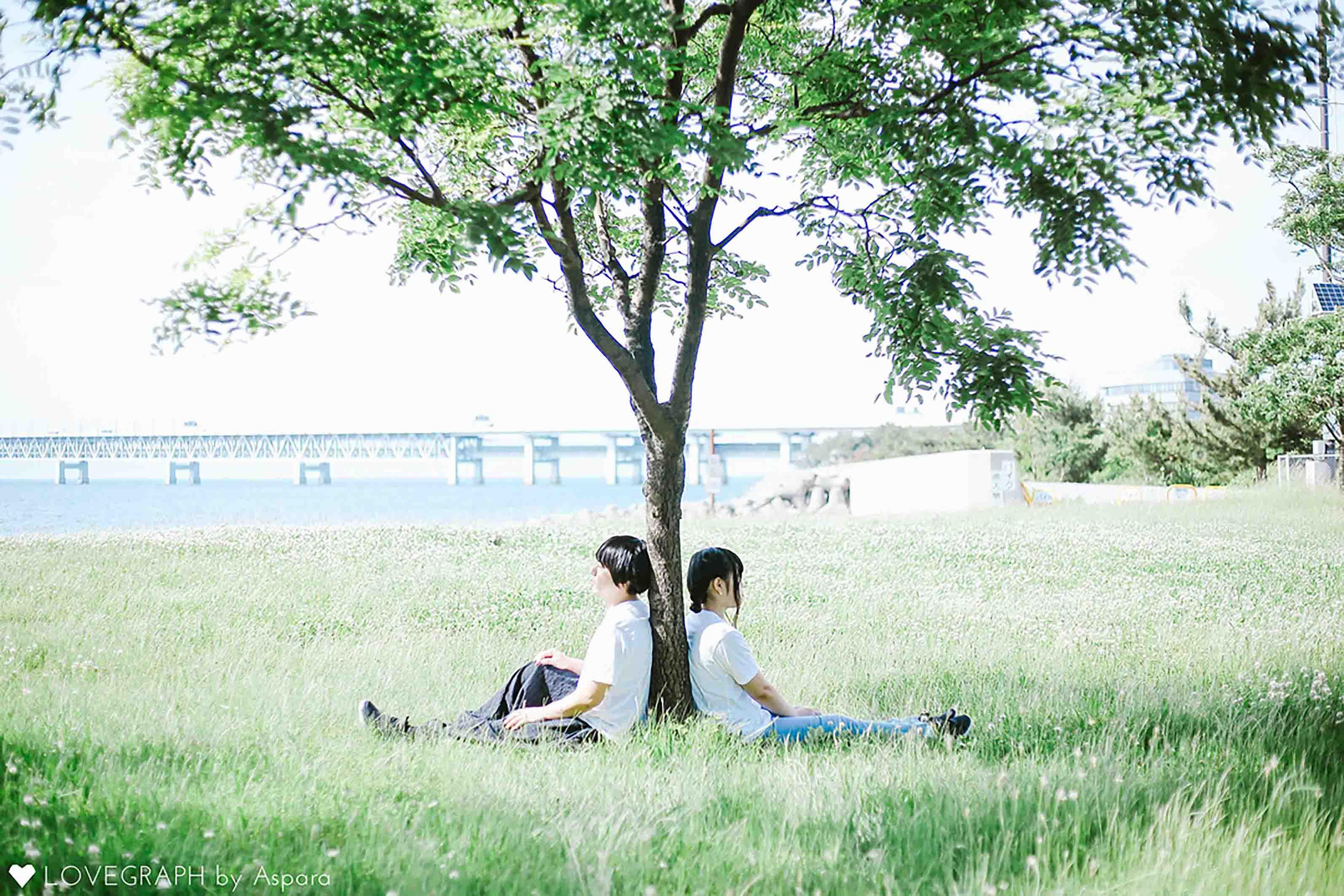樹木に背中をあずけ座るカップル