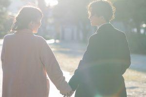 木漏れ日_笑顔で手を繋ぐカップル