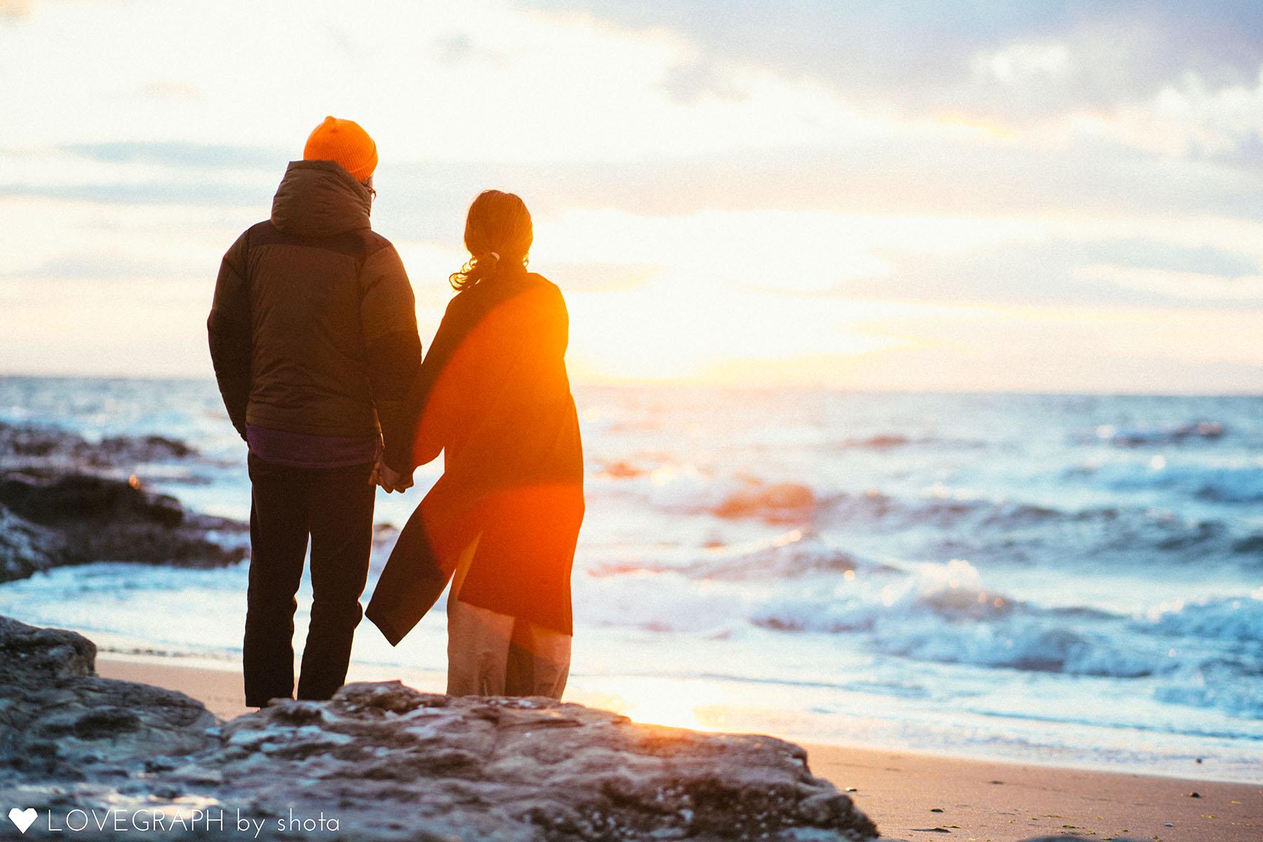 冬の海を眺めるカップル