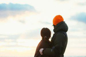 寄り添って夕日を眺めるカップル