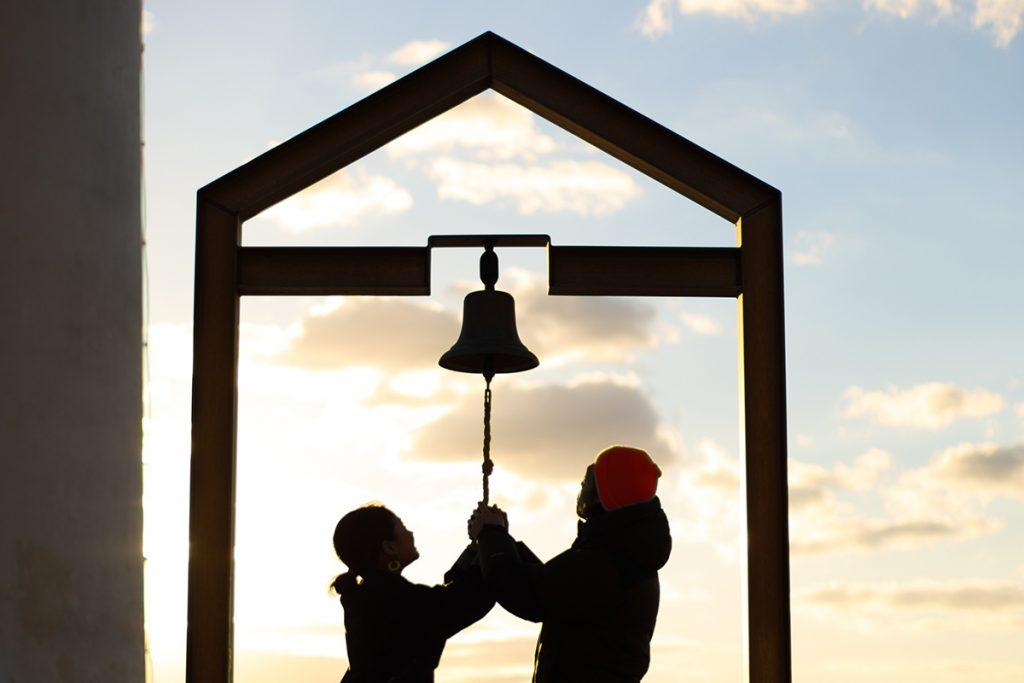 鐘を鳴らすカップル夕焼け