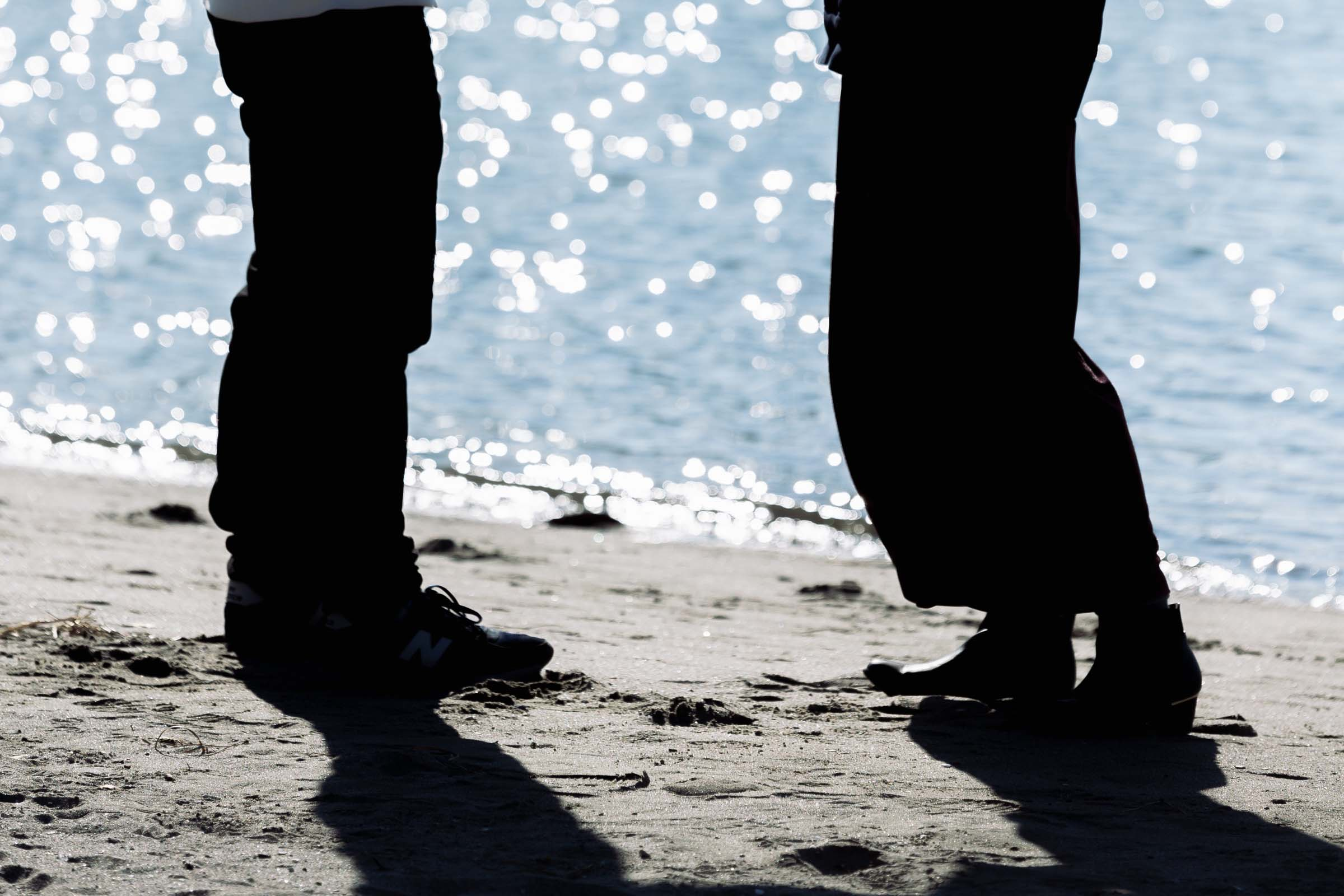 砂浜向かいう男女の足元