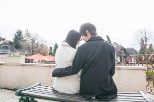 ベンチで額を寄せるカップル