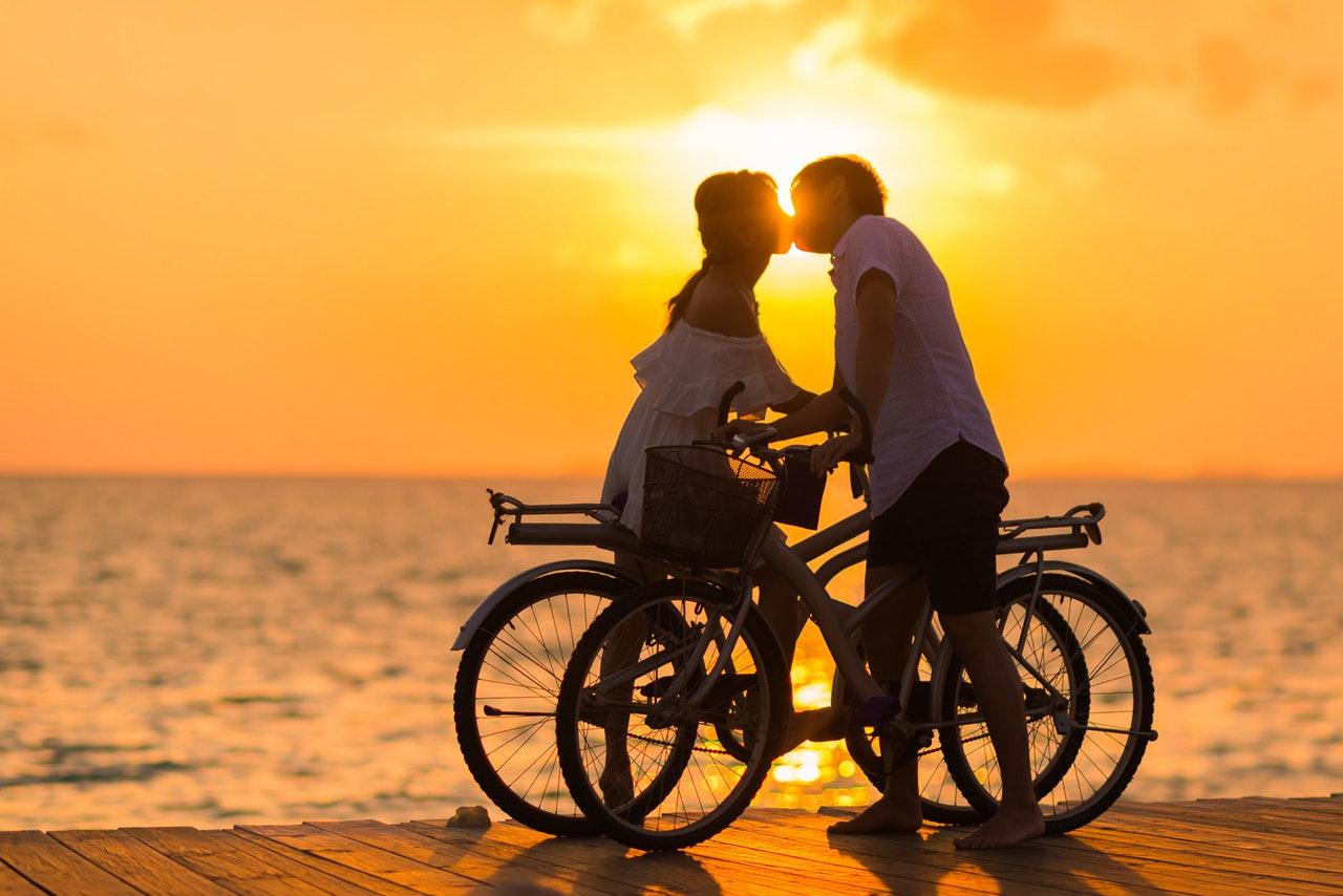 夕日の見える海辺でキスするカップル