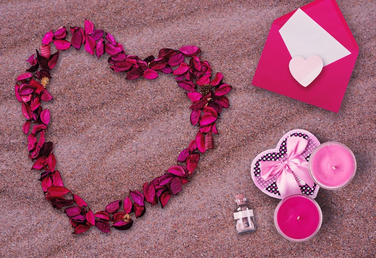 砂の上にピンクの花びらで作られたハートとピンクの小物