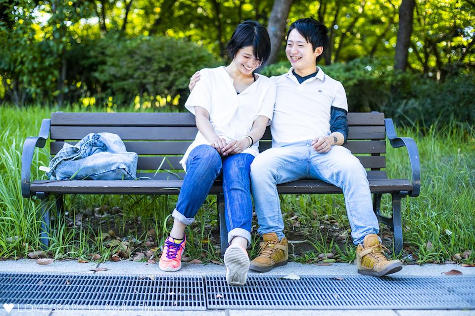 並んでベンチに座るカップル