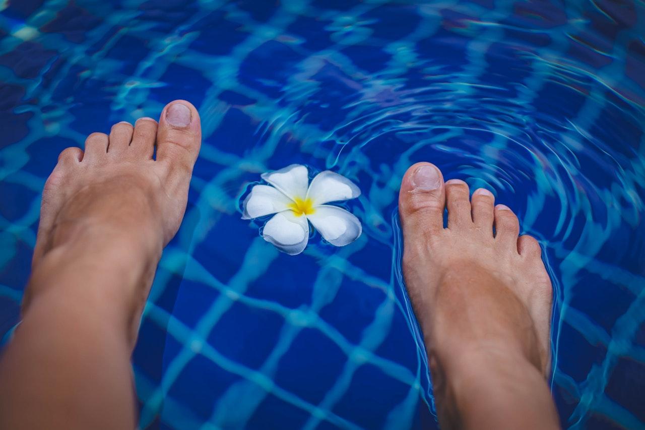 素足と水に浮かぶ花