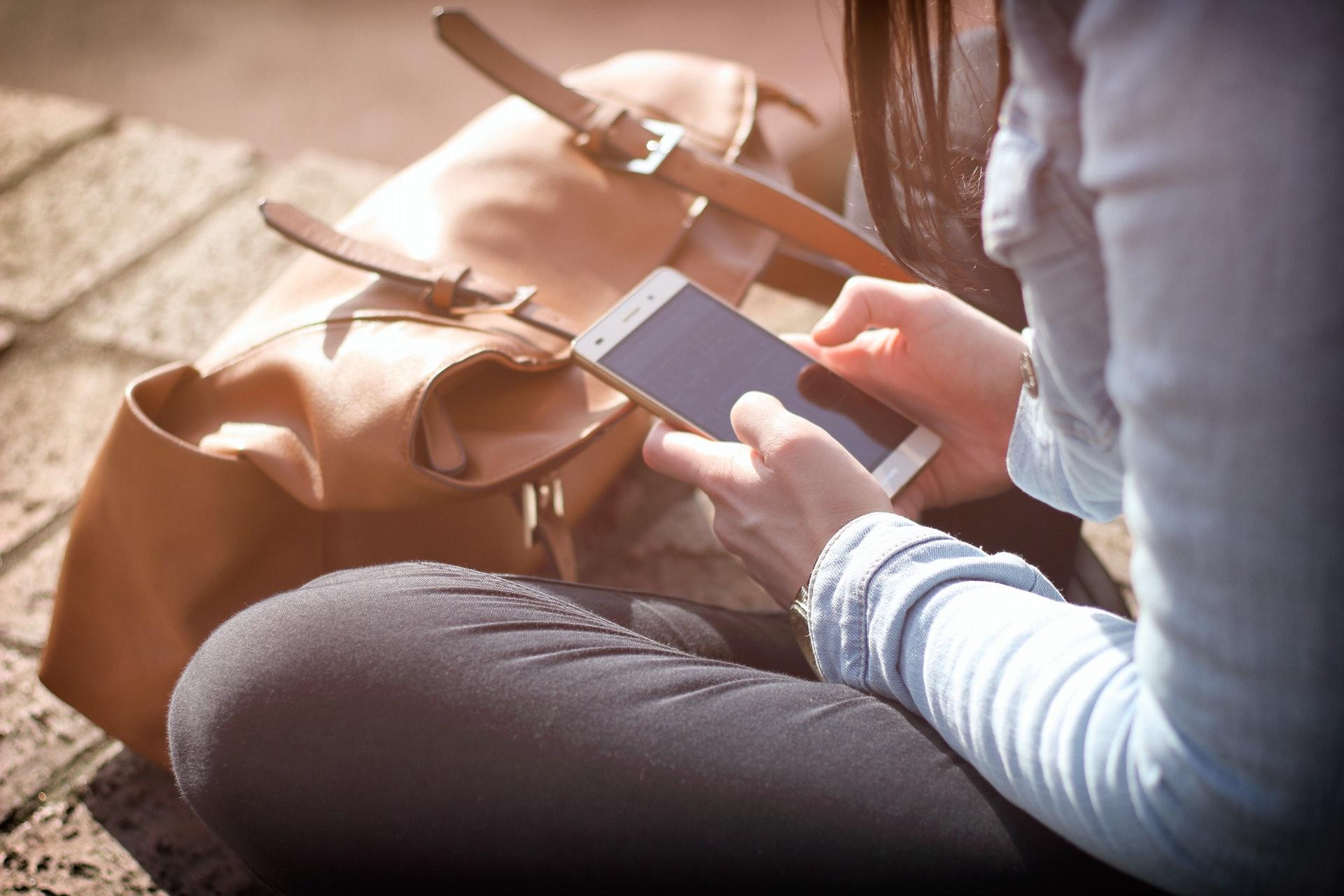 道端でスマートフォンを見る女性