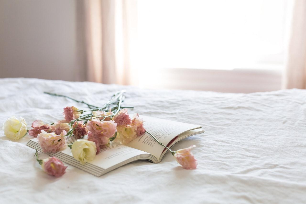 ベッドの上の本と花