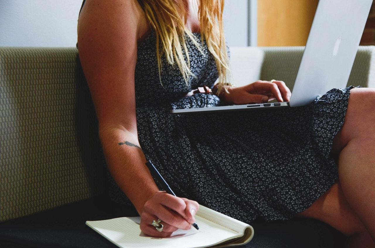 PCを見てノートをチェックする女性