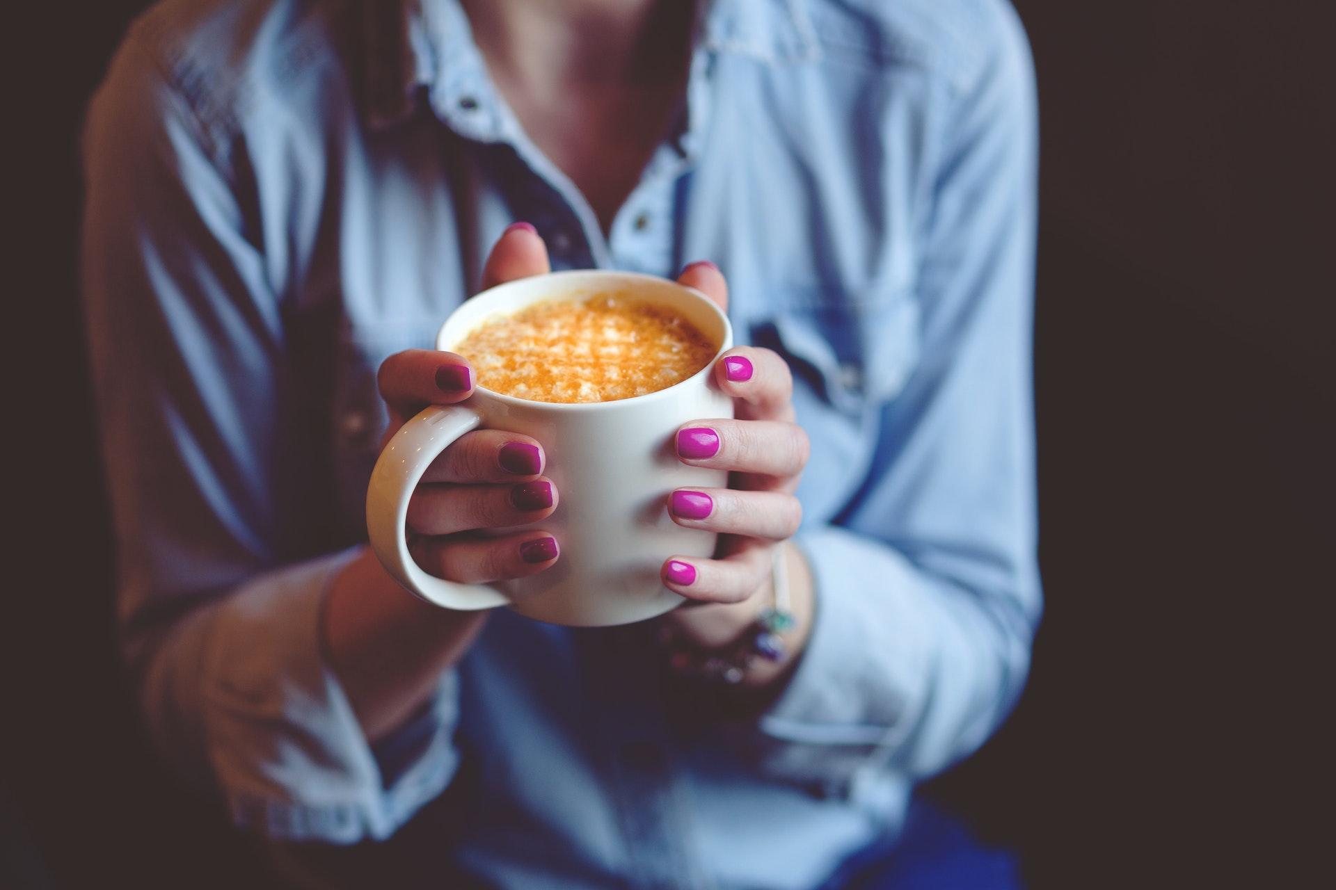 コーヒーを手にする女性