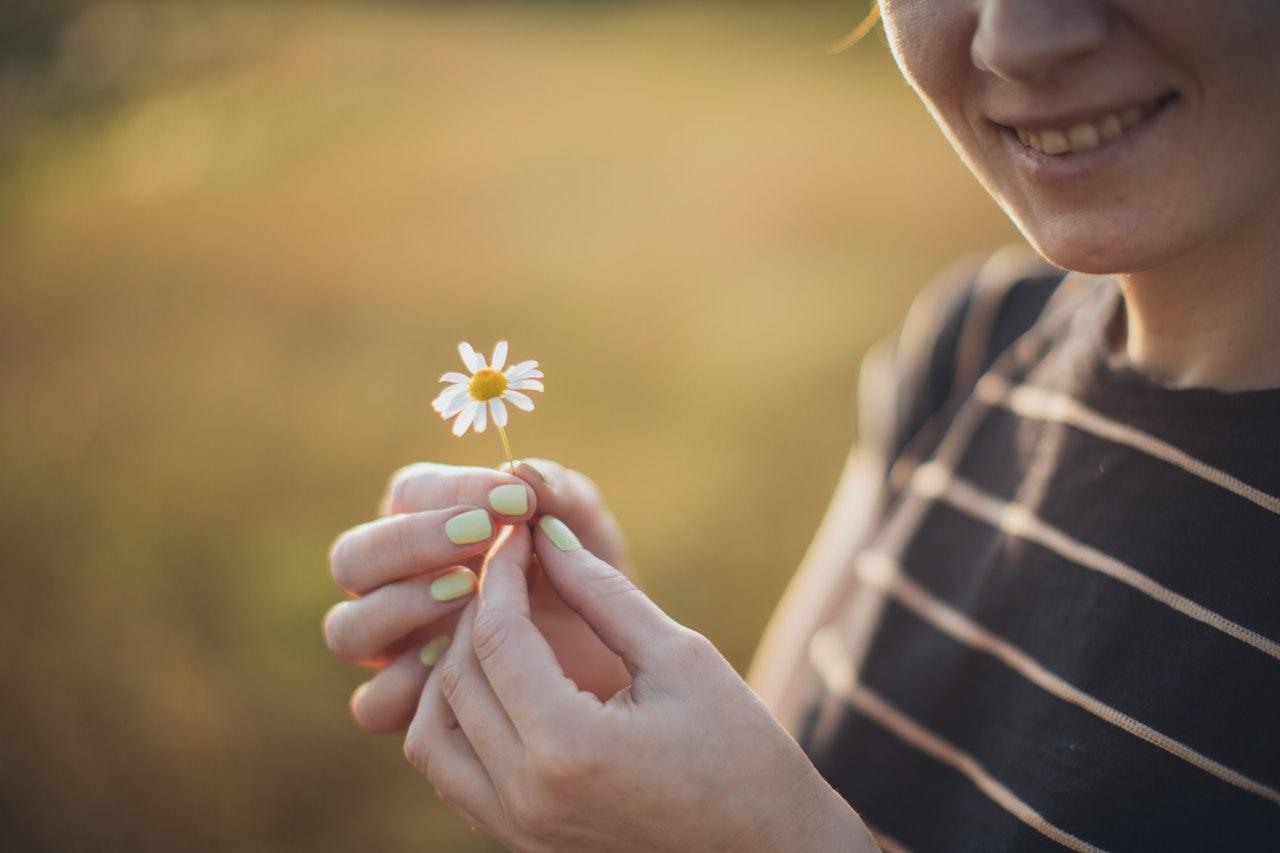 小さな花を手にする女性