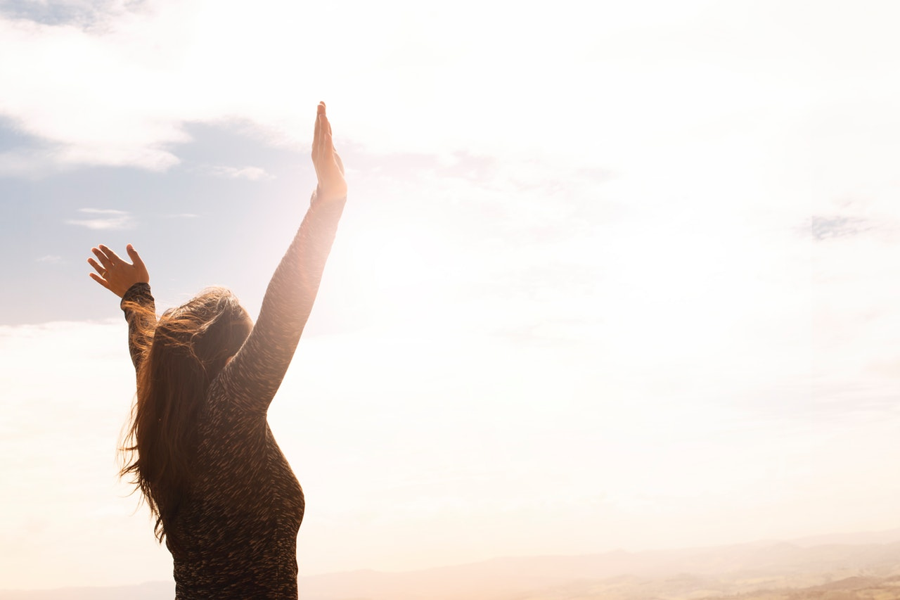空に向かって手を挙げている女性