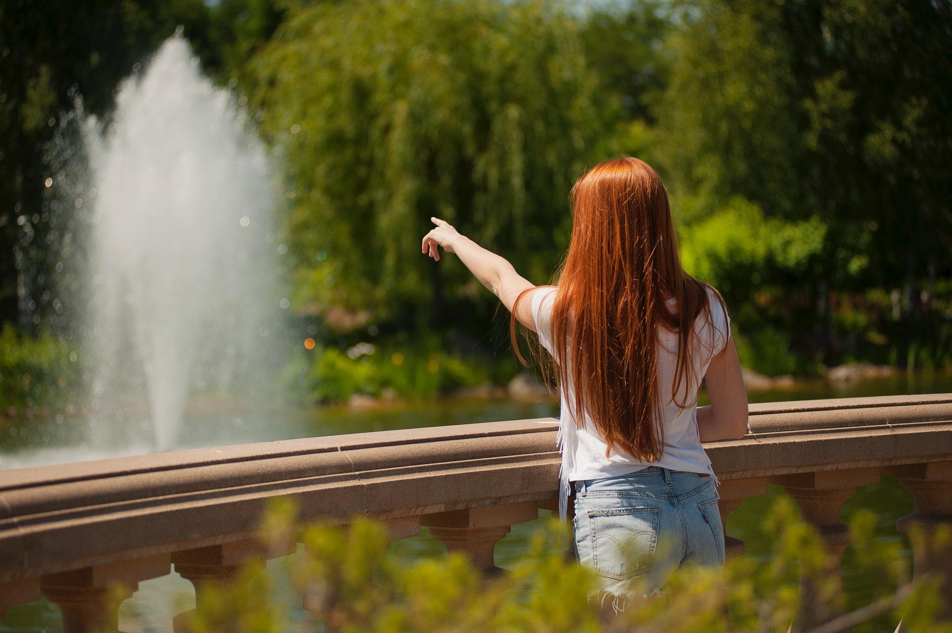 噴水を指さす女性