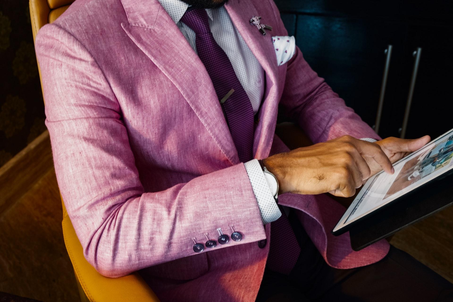 紫のスーツに身を包んだ男性