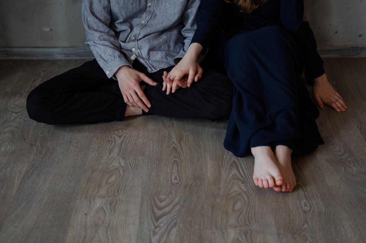 手をつなぎ座っている男女