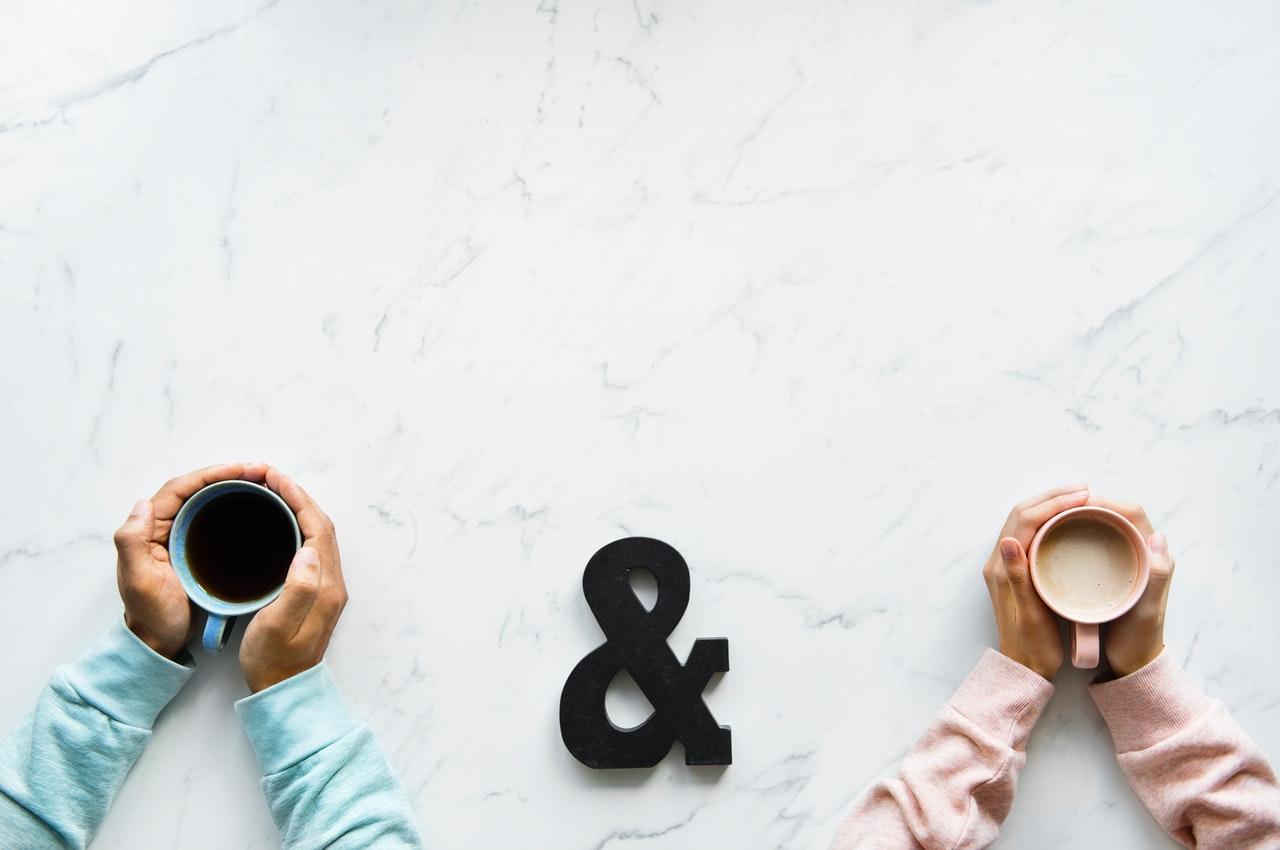 コーヒーを手に並んでいる男女