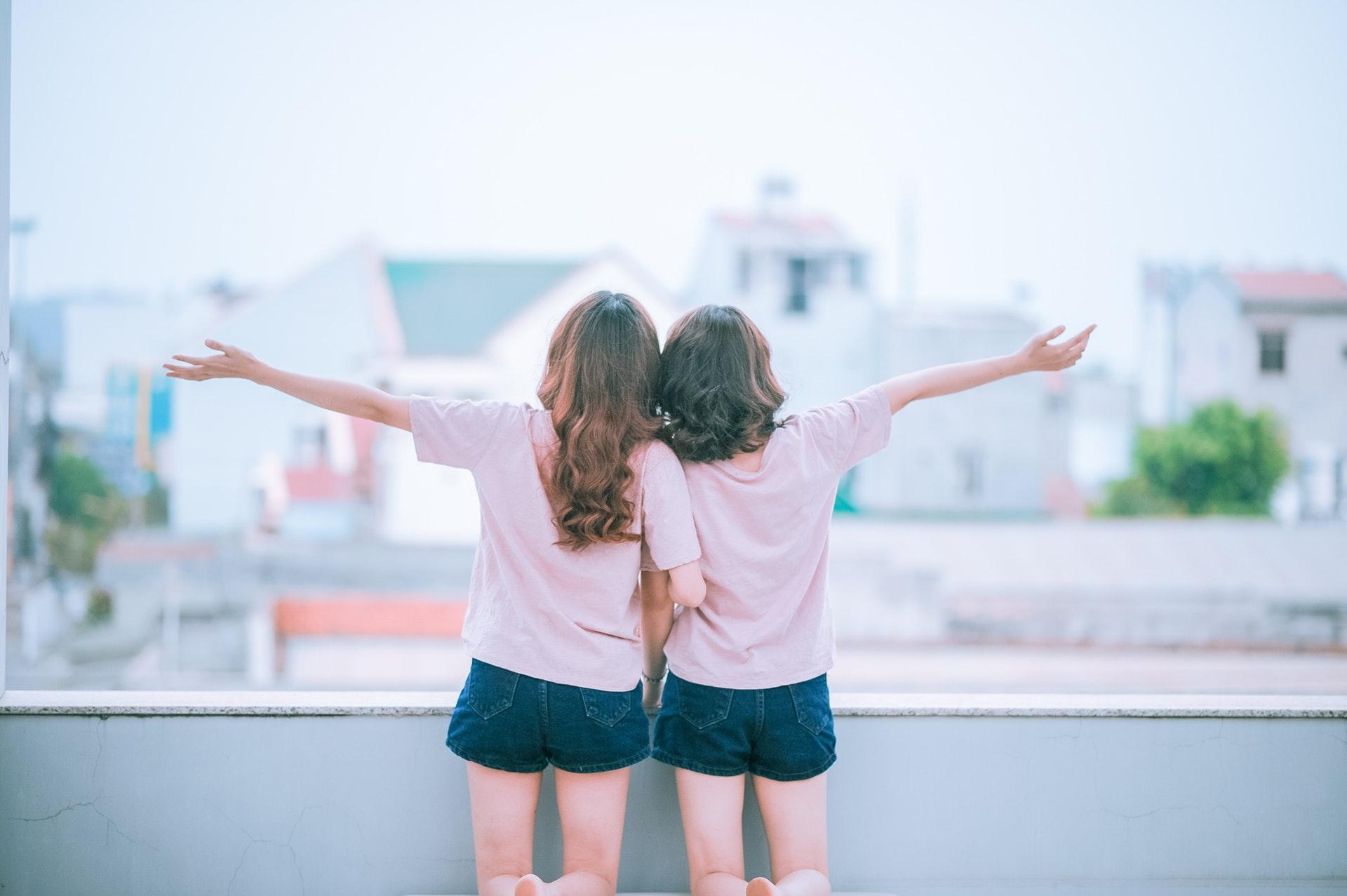 女性2人が両手を広げて立っている