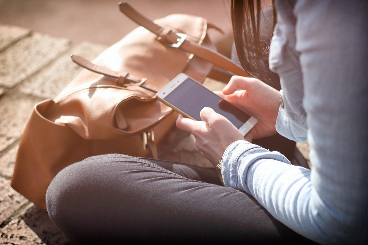 座ってスマートフォンを見入る女性