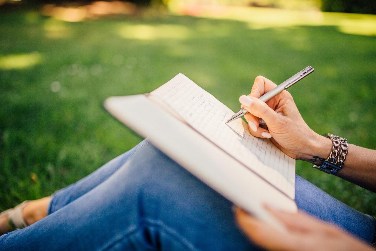ノートにペンを持つ人