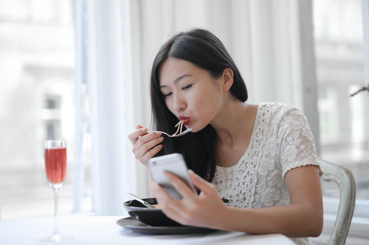 食事中スマホを見る女性