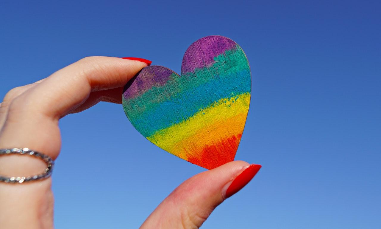 虹色のハートを見つめる人