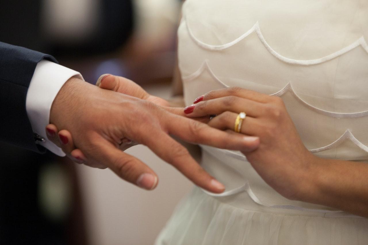 新郎に指輪をはめる新婦