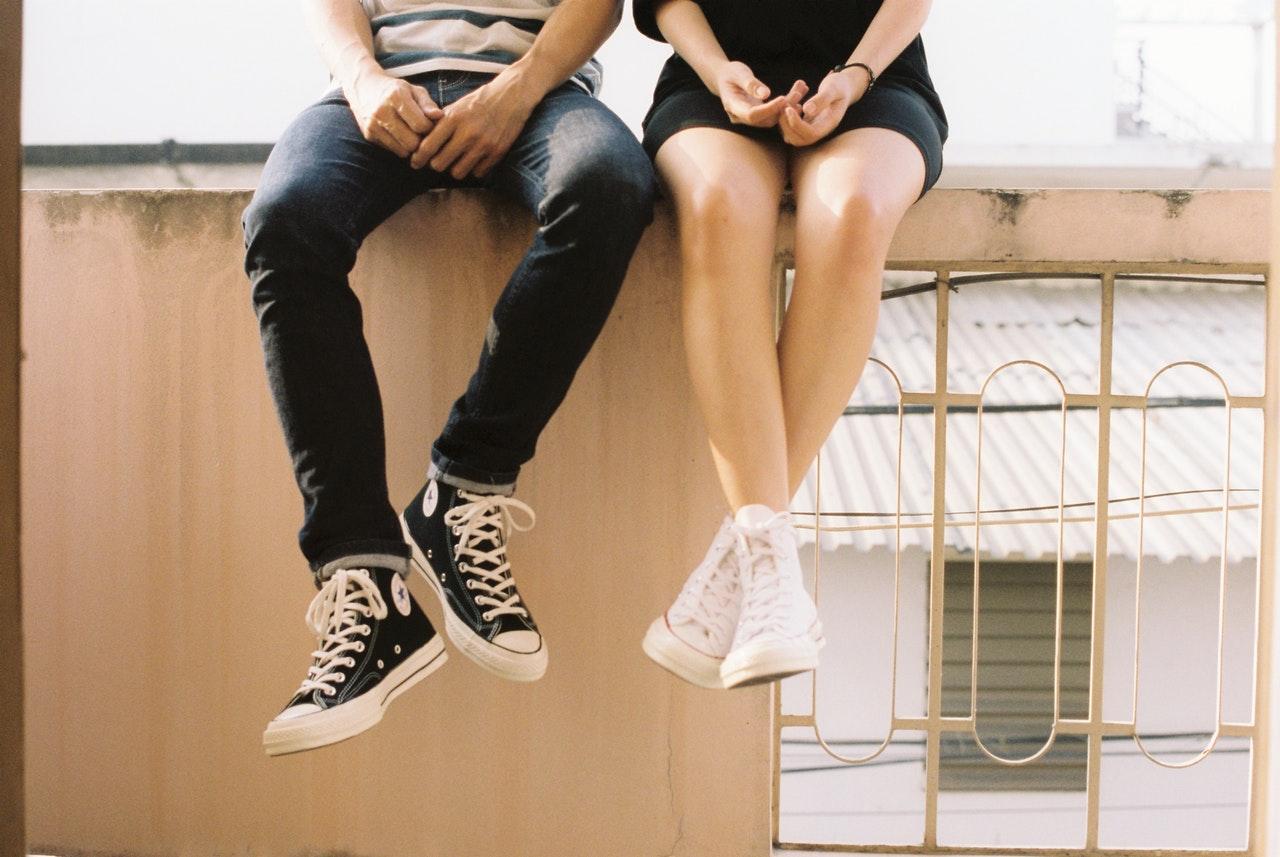 壁に腰掛けるカップル