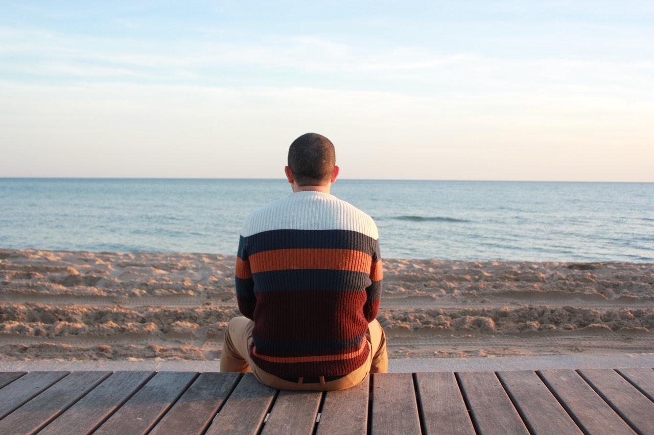 寂しく海を見つめる男