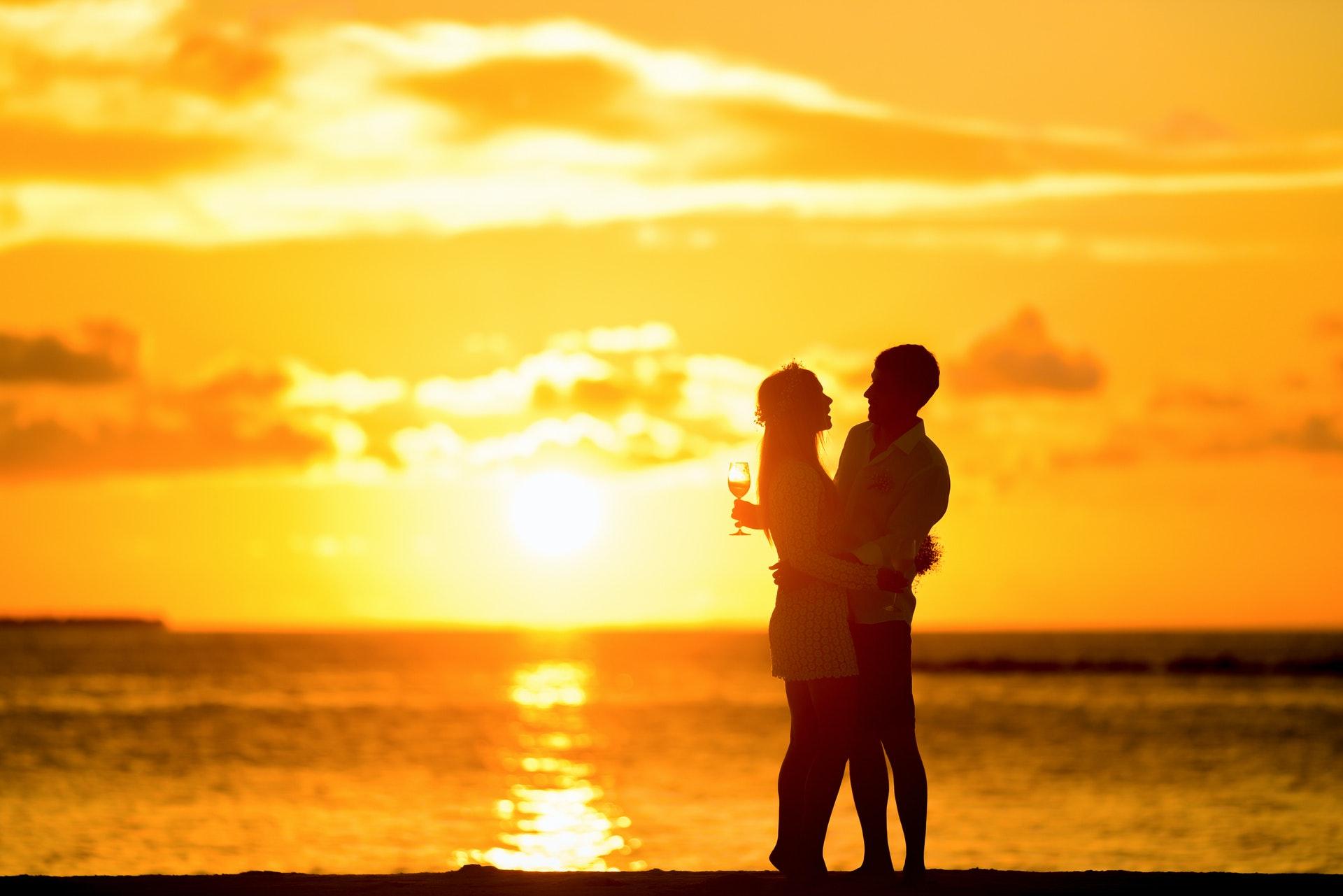 夕日をバッグにハグするカップル