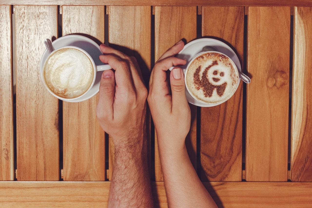 カップルの手とコーヒーカップ