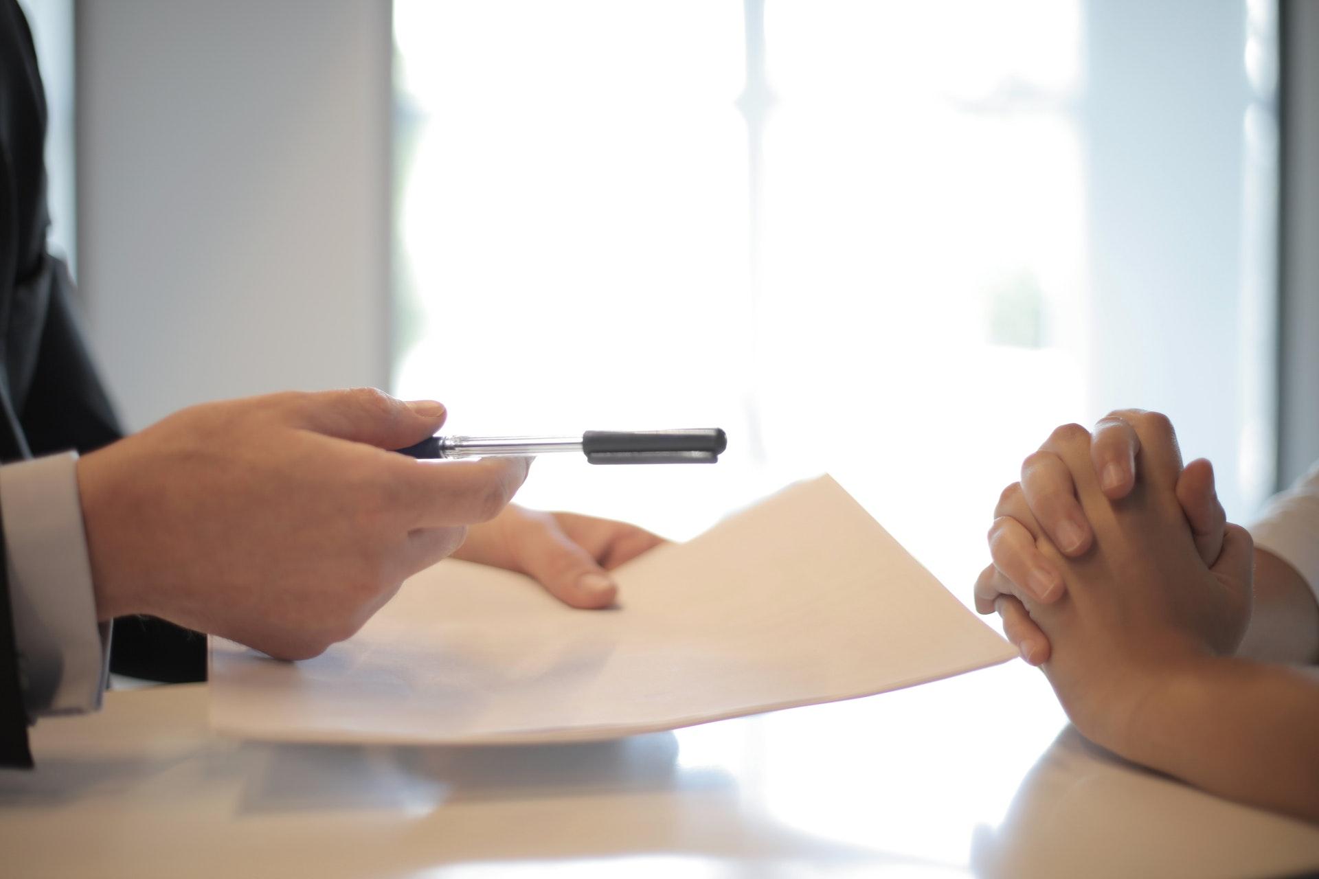 書類とペンを渡す手